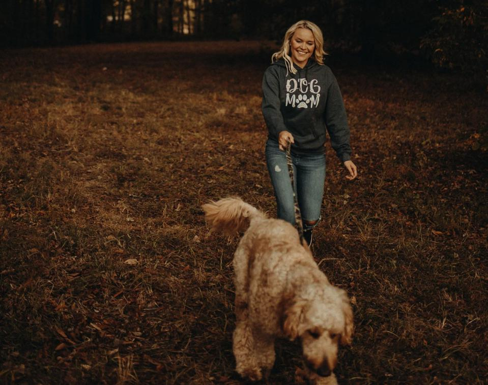 A woman walking her dog while wearing a Pawz Dog Mom hoodie