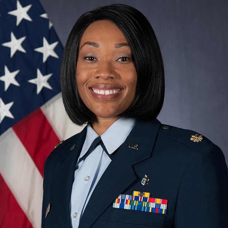 Crystal McLeod in Military Suit in front of blue background with a flag in waving left-hand corner.