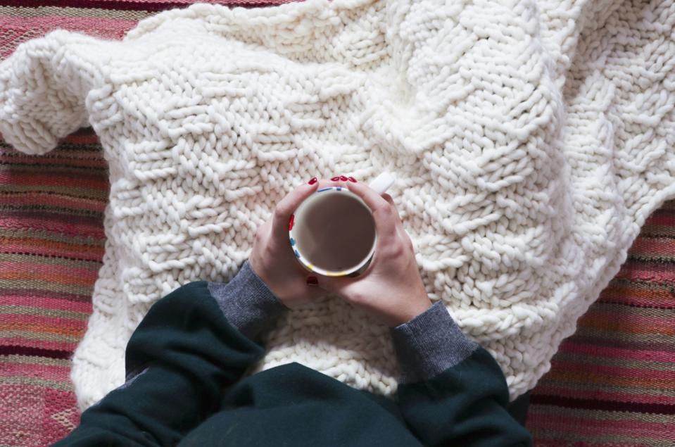 A mom relaxing under her handmade We Are Knitters blanket