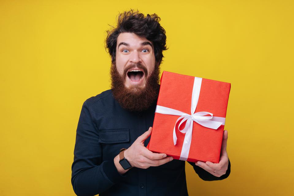 Handsome bearded man, looking excited at camera, holding a gift box, and standing over yellow background
