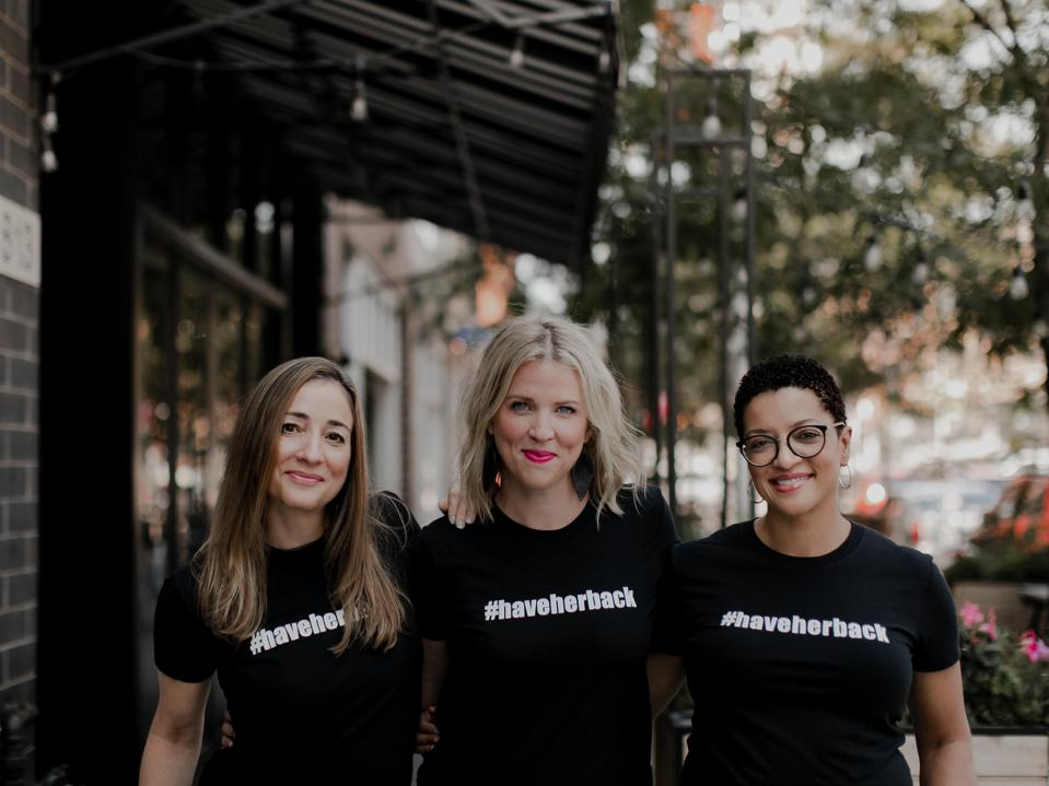 Three women stand together outside in black t-shirts reading #HaveHerBack.