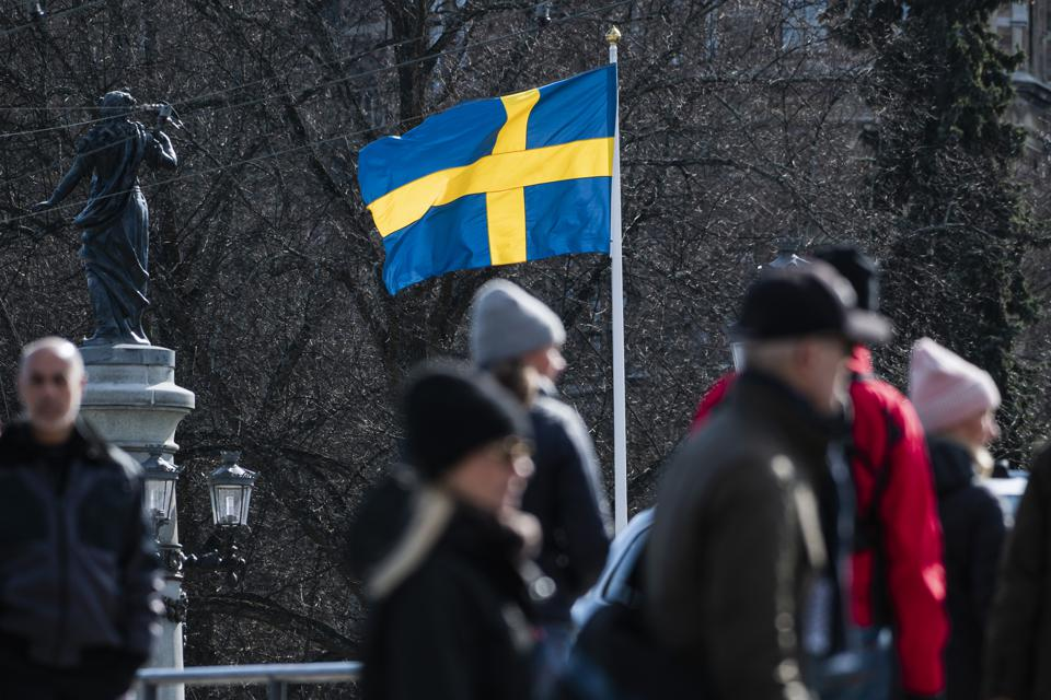 The Swedish flag and locals walking in Stockholm, Sweden