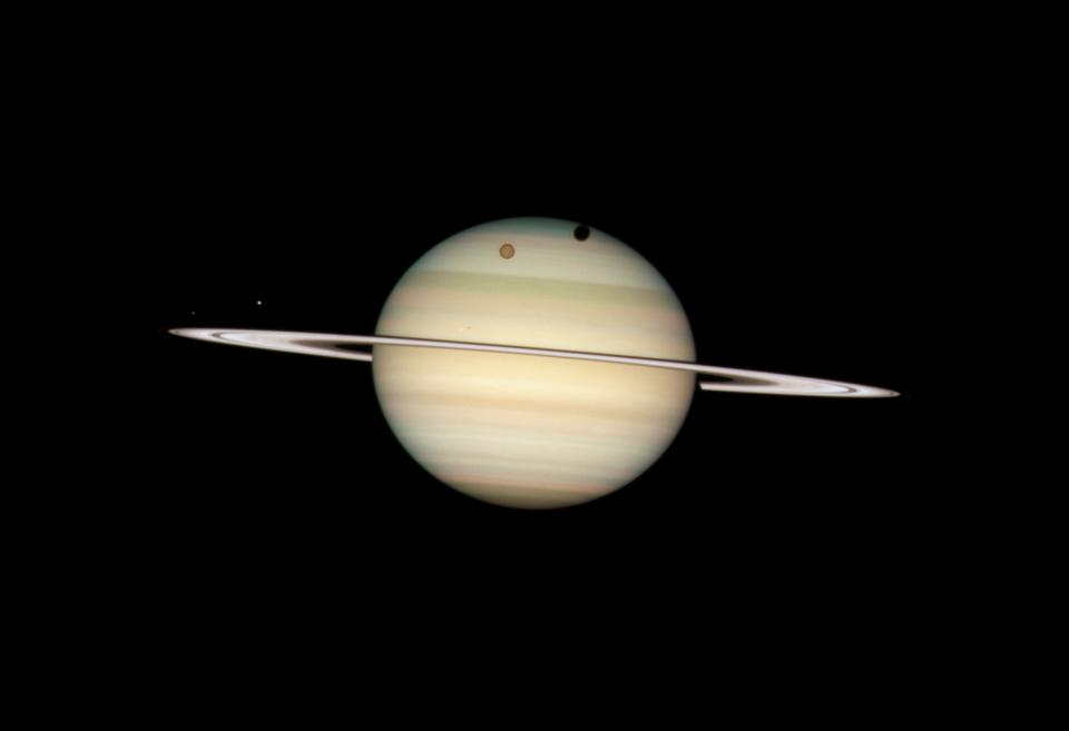 On February 24, 2009, the Hubble Space Telescope took a photo of four moons of Saturn passing in front of their parent planet. In this view, the giant orange moon Titan casts a large shadow onto Saturn's north polar hood. Below Titan, near the ring plane and to the left is the moon Mimas, casting a much smaller shadow onto Saturn's equatorial cloud tops. Farther to the left, and off Saturn's disk, are the bright moon Dione and the fainter moon Enceladus.