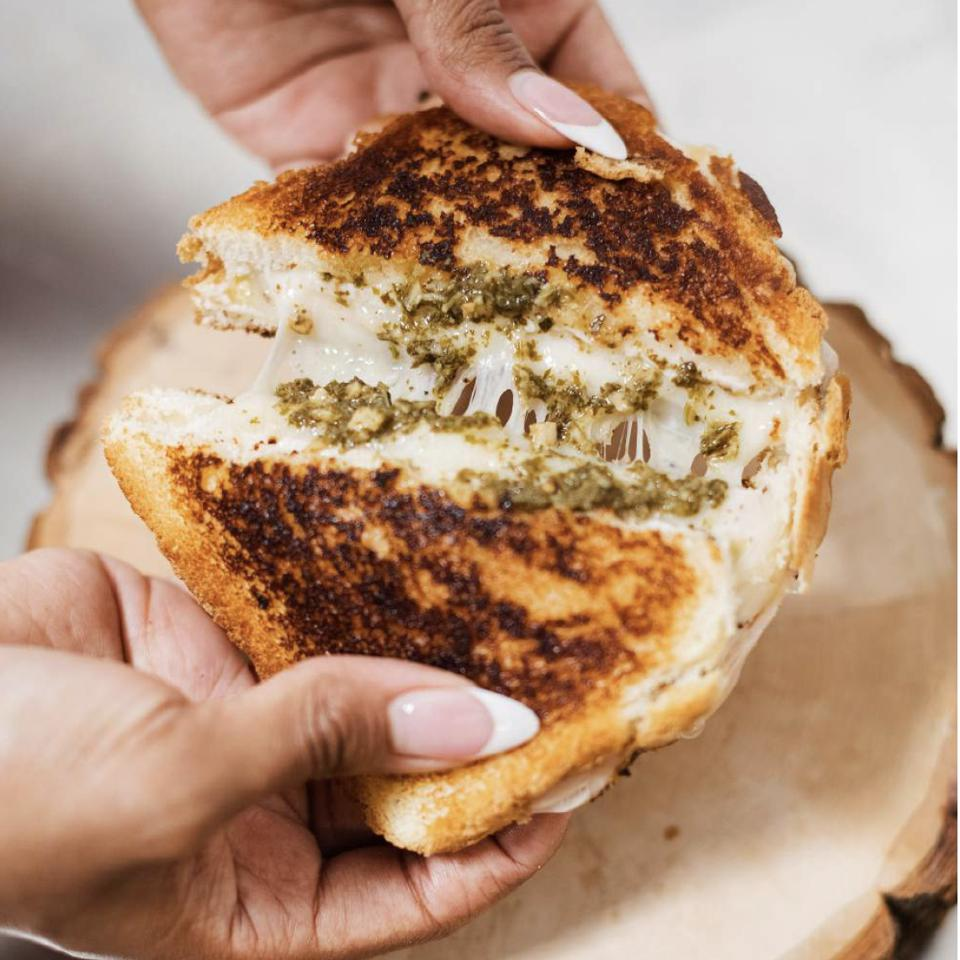 Grilled Cheese sandwich being broken by two hands over a wood log.