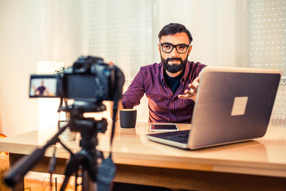 Man sitting at the desk in front of the camera making video.