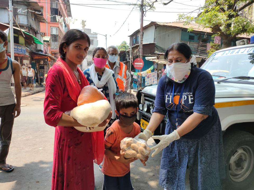 A woman wearing a face mask offers food to a small child and young woman.