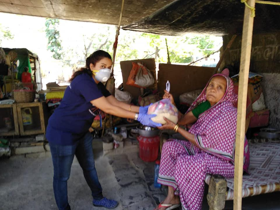 A woman with a face mask hands a basket of fruit to a woman in a pink sari.