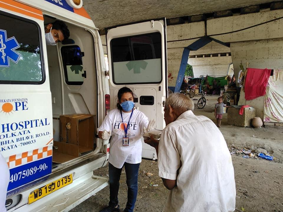A woman in a face mask stands outside a van reading ″hospital,″ talking to an elderly man