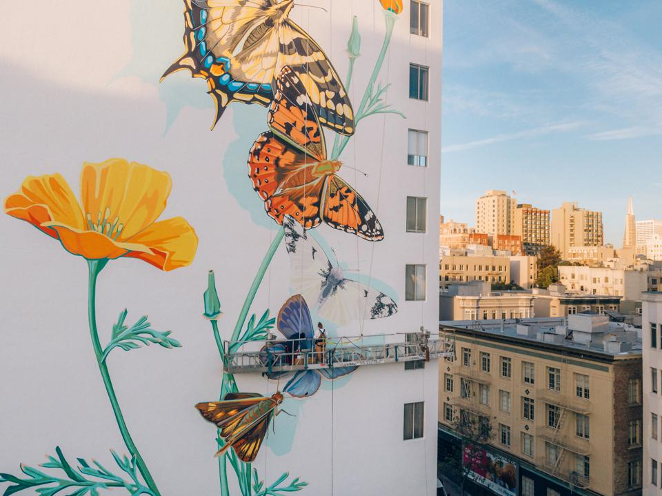 An artist at work on Ink Dwell's Monarch Migrating Mural for 455 Hyde Street project in San Francisco.
