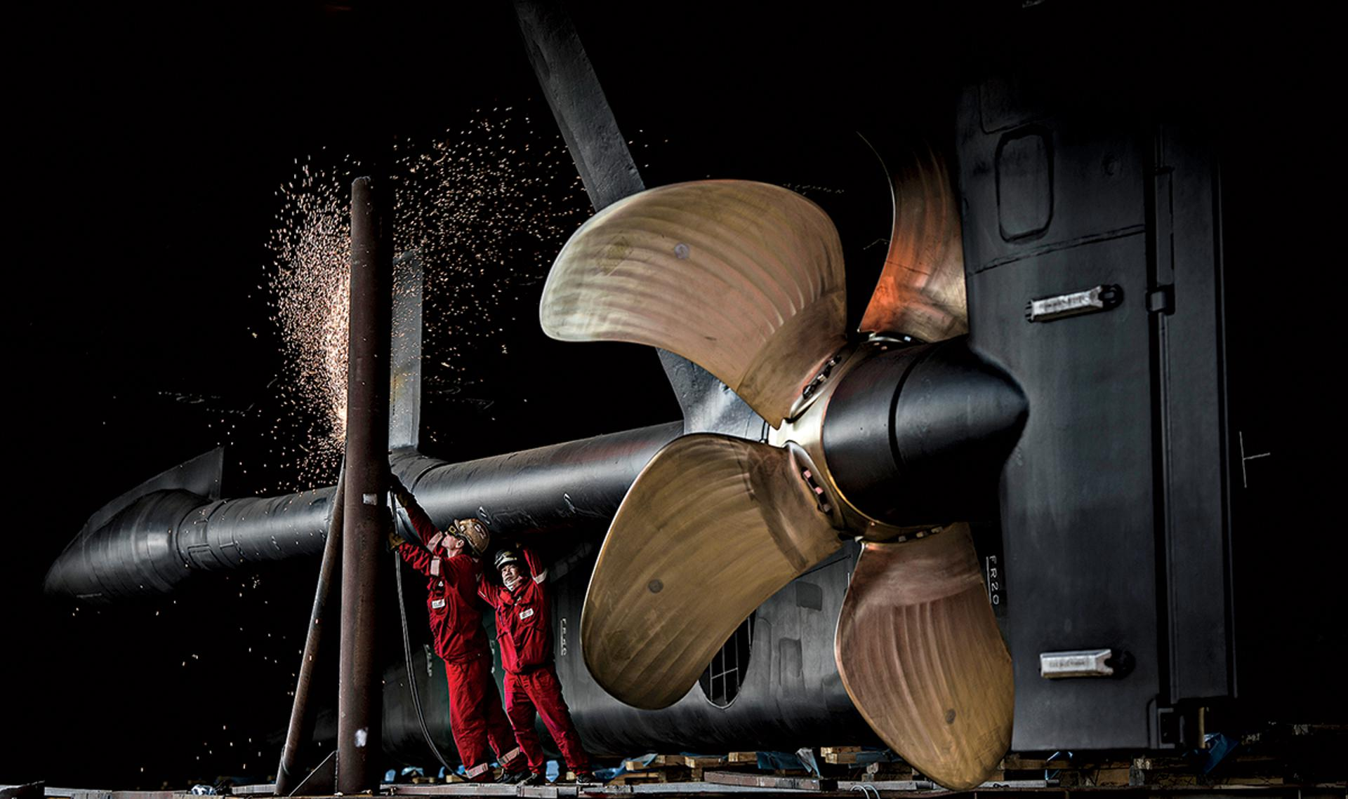 Spinning Their Wheels: Shipyard workers affix a mammoth propeller to Rev's stern. Construction is delayed due to the COVID-19 outbreak.
