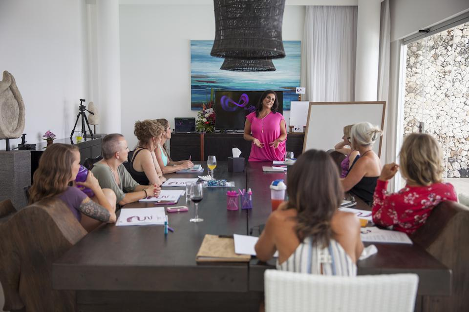 businesswoman lecturing in a conference room full of other women