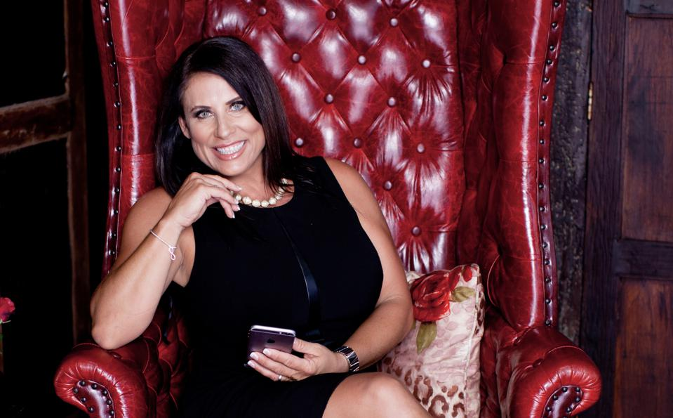 business woman sitting in red chair texting and smiling