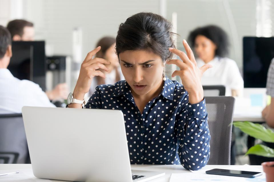 Upset female office worker reading unpleasant message