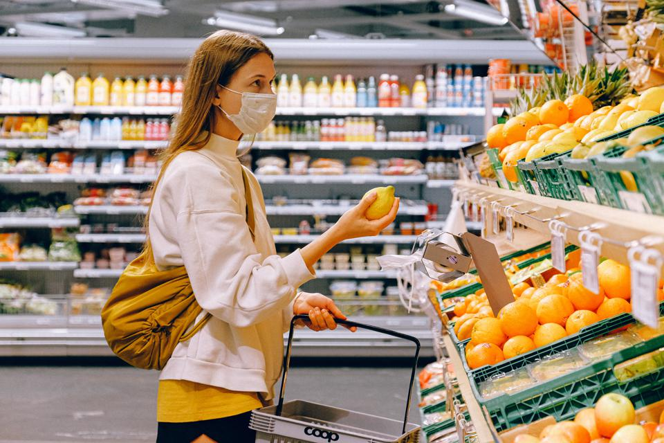 Woman shopping at a grocery store holding a lemon