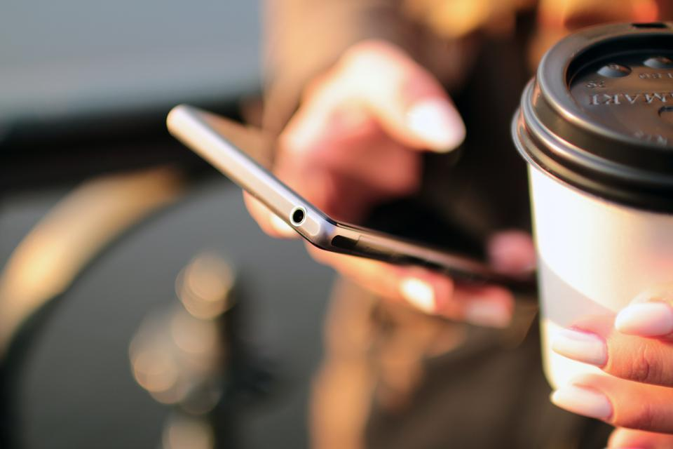 Someone holding a coffee cup and a mobile phone