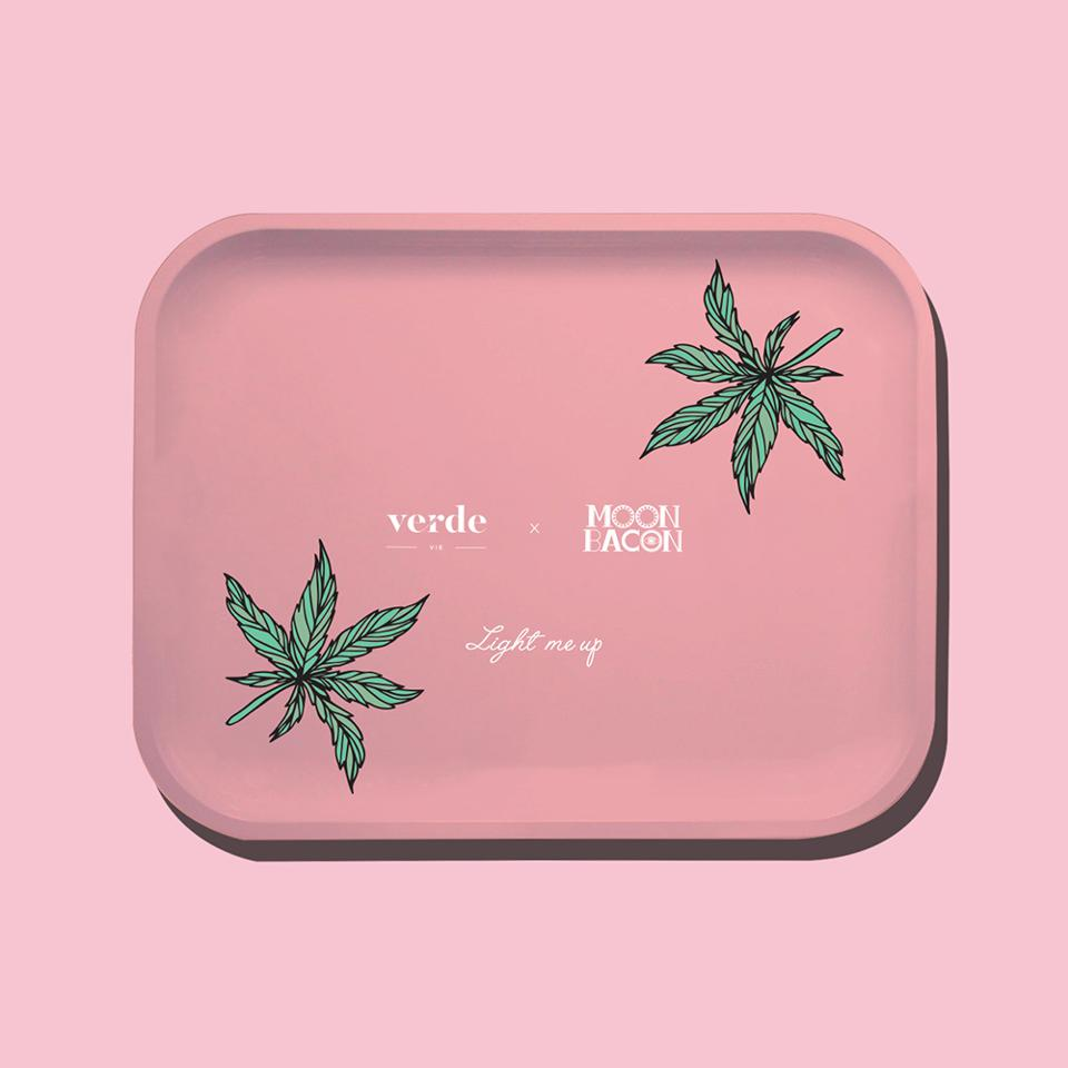 a pink rolling tray with cannabis leaves