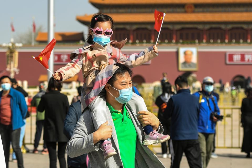 People walking through Tiananmen Square.