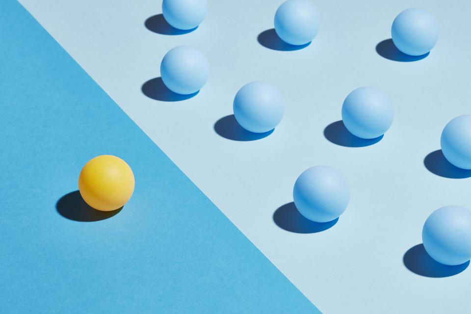 A Yellow sphere sits apart from a group of blue spheres.