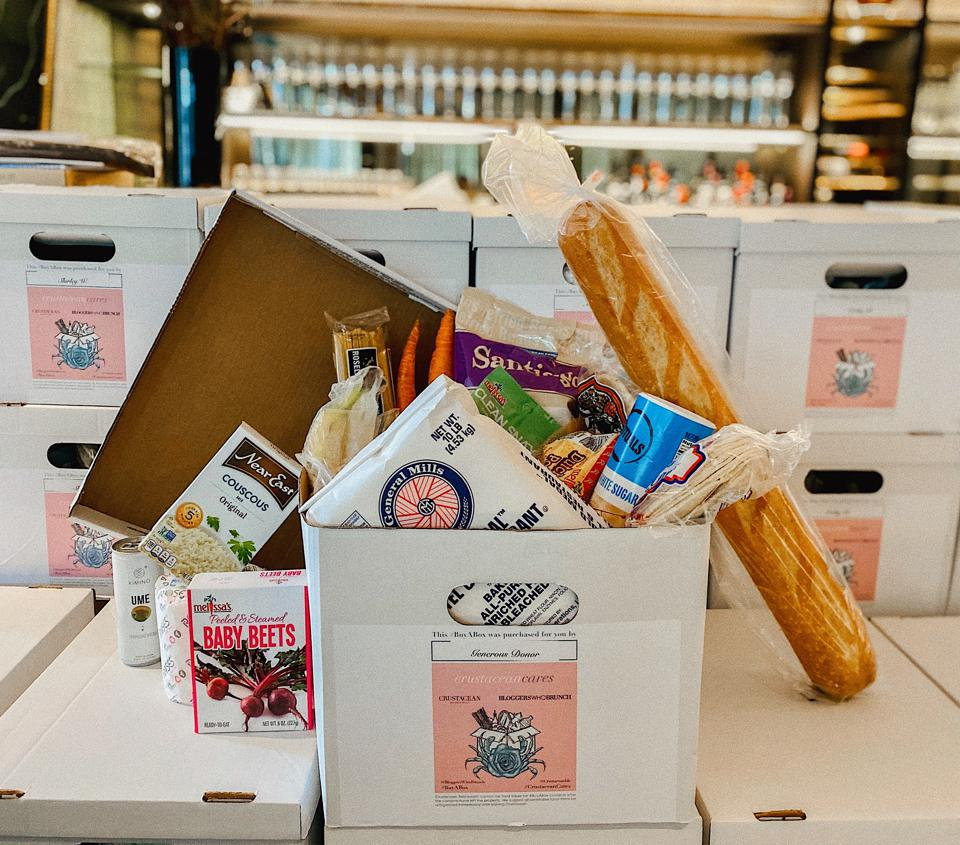 Bloggers Who Brunch and Crustacean team up to give boxes of food to those who have lost work in the service industry.