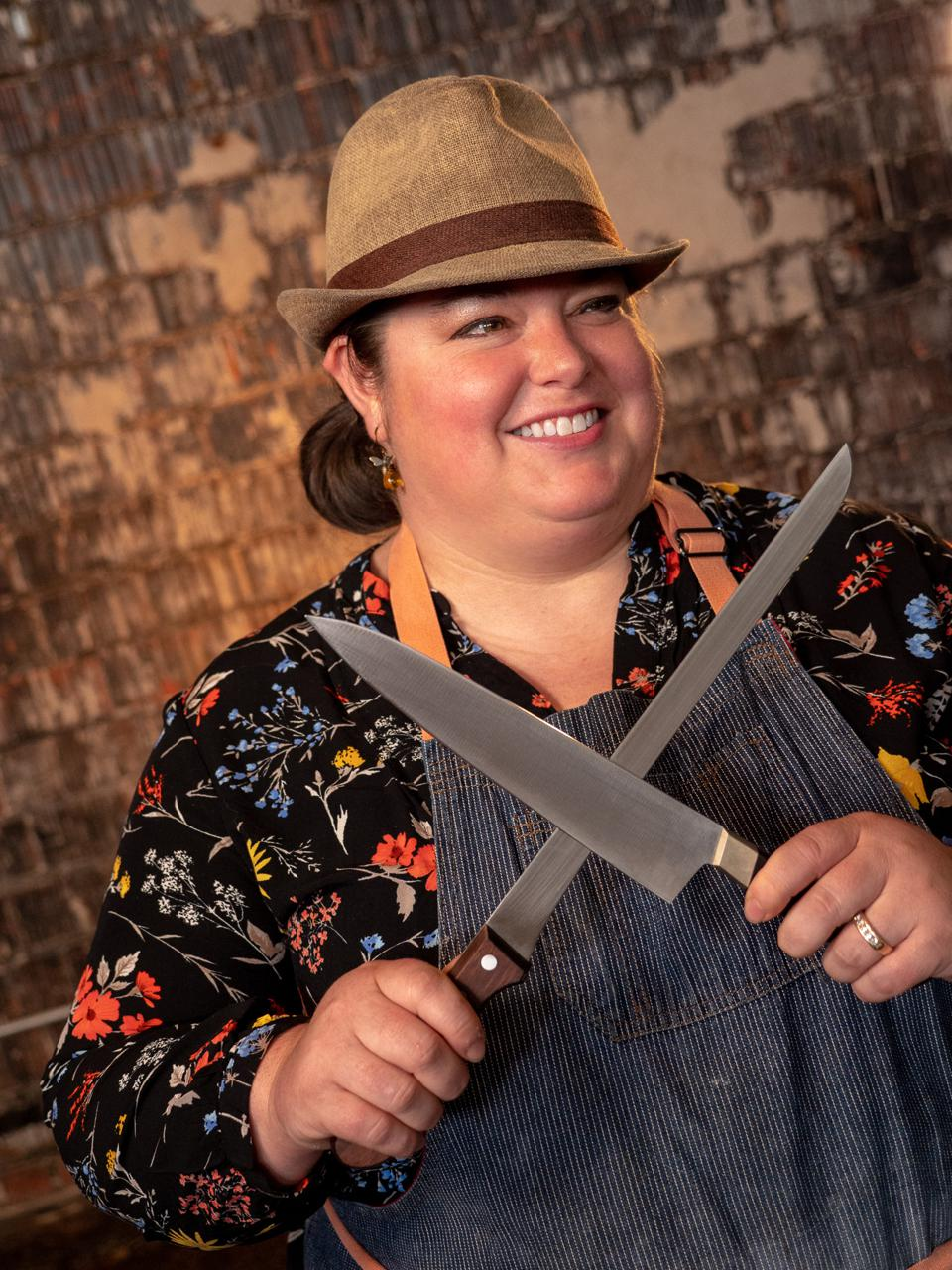 a woman holding two knives