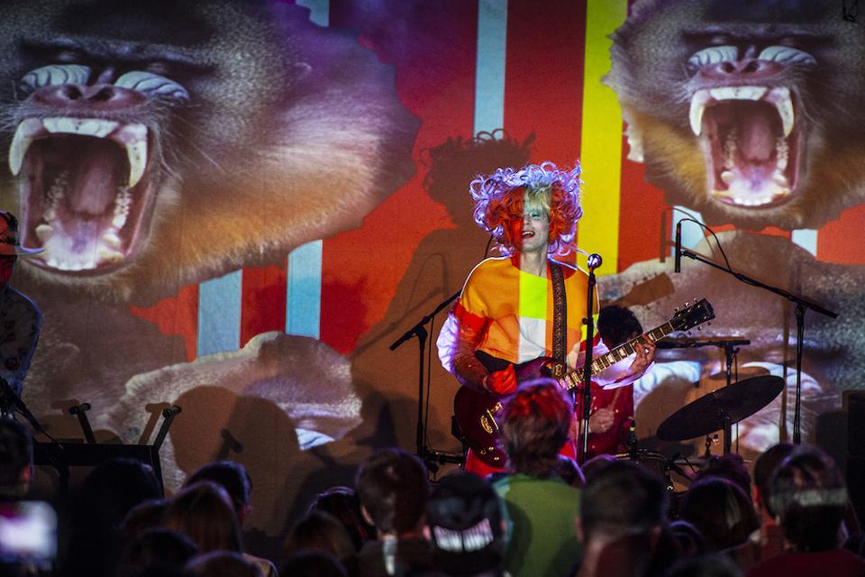 A psychedelic image of the band Of Montreal playing.