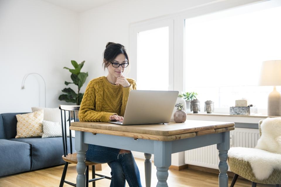 Woman sitting at table, using laptop