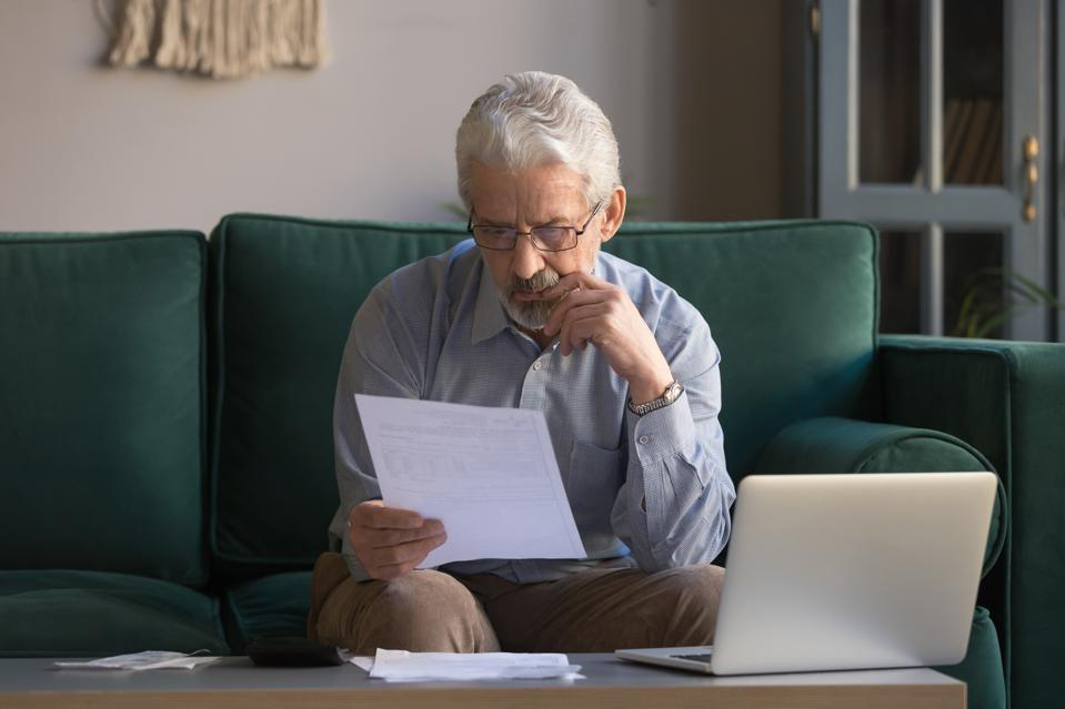 Serious mature man sitting on couch received invoice analyzes expenses