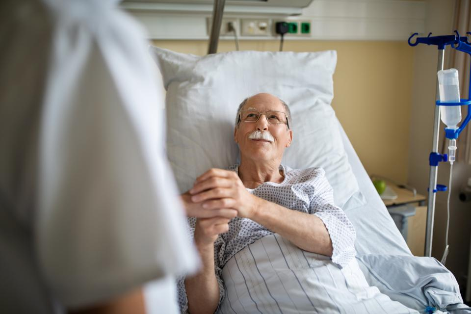 Senior man holding hand of female nurse in hospital room. Female nurse talking with old male patient in hospital ward.