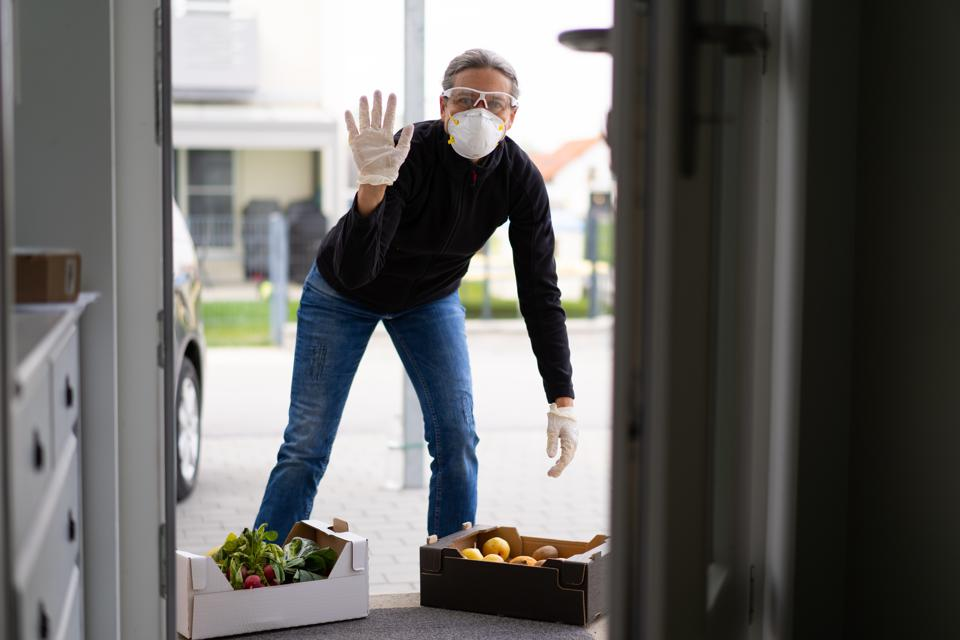 A woman wearing protective gear drops off fresh food to a neighbor's doorstep.