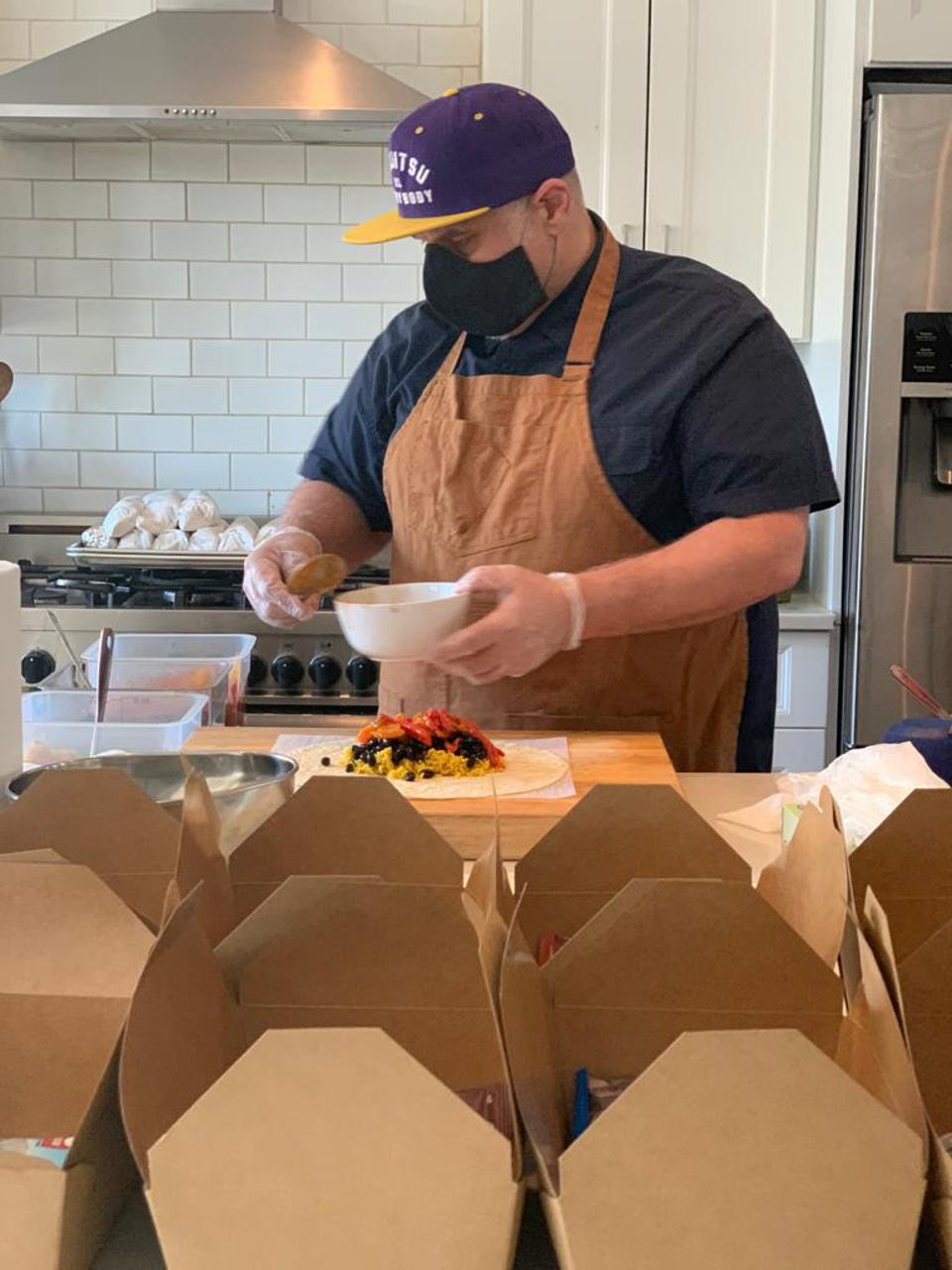Big Love Catering's Felipe Avalos makes rice and bean burritos for hospital workers.