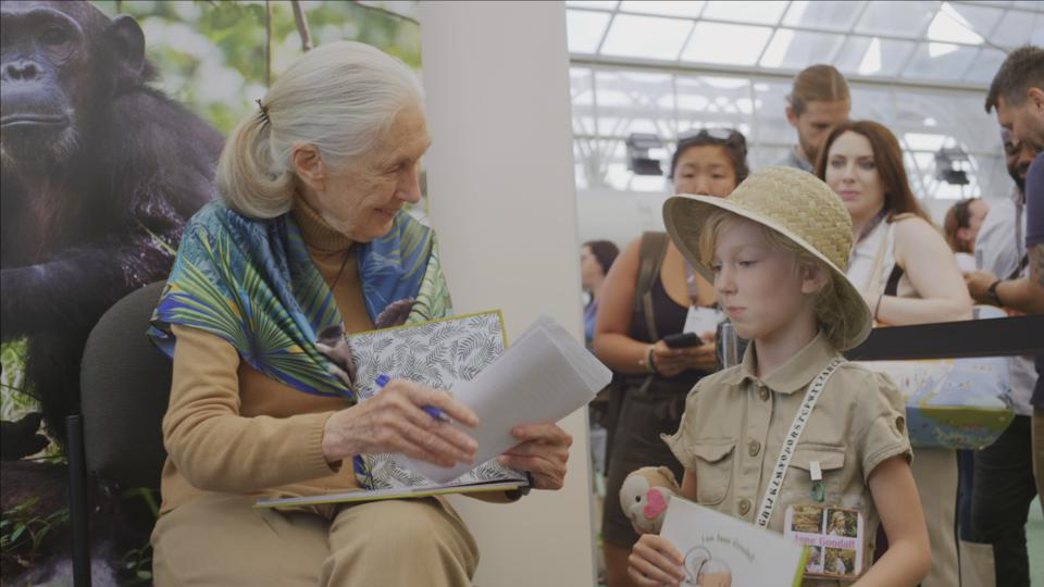 Jane Goodall signing a book for a young girl at Esri Conference in 2019.