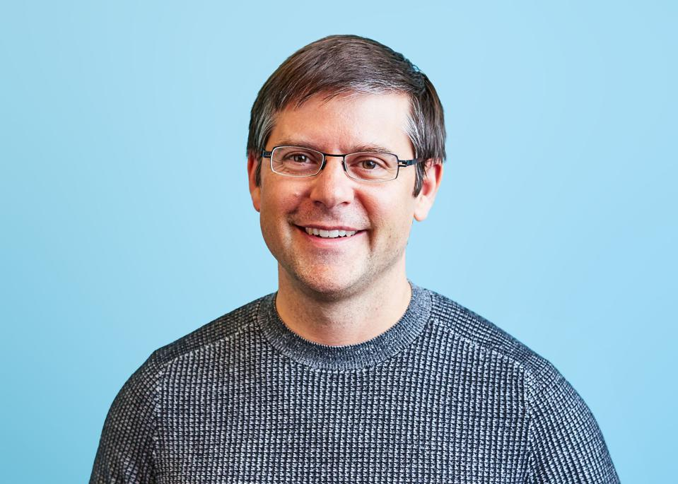 Brad Hoover, CEO, Grammarly. Middle aged man with glasses and a grey sweater.