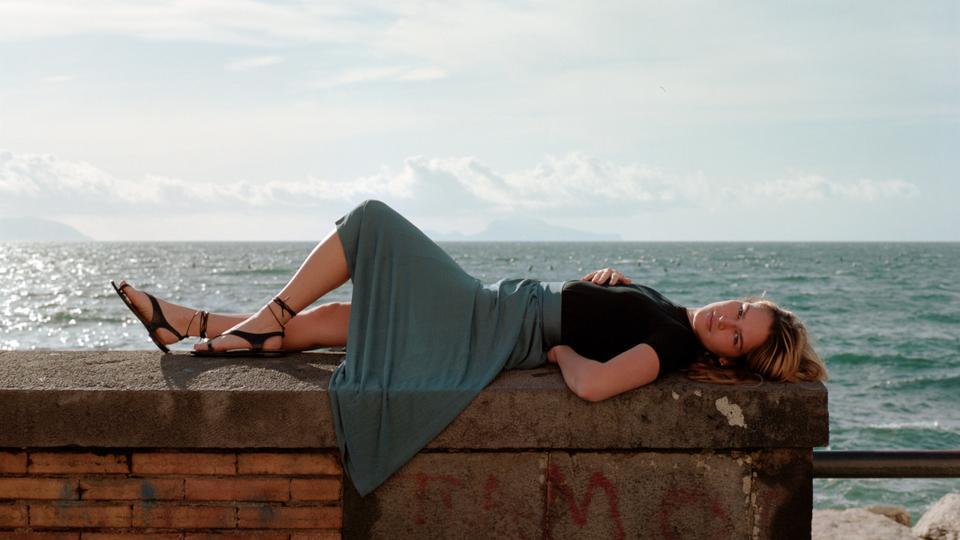 Model lounging on a brick wall along Italian seaside wearing a green skirt, black shirt, and black sandals.