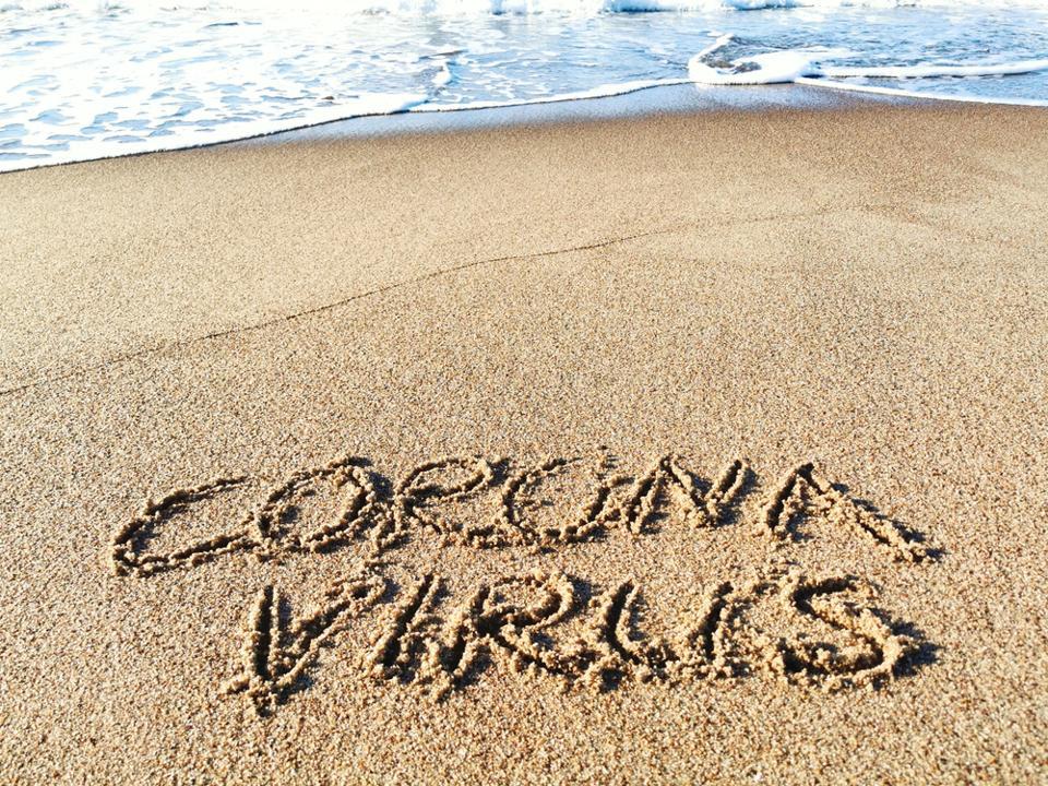 ″Coronavirus″ written in sand on a beach