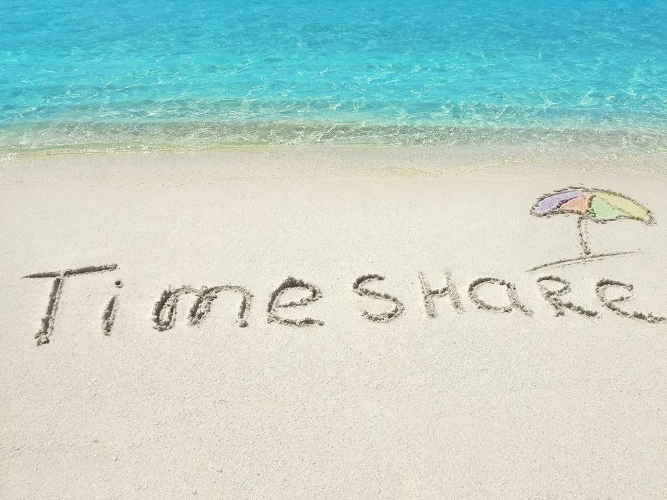 ″Timeshare″ written in beach sand