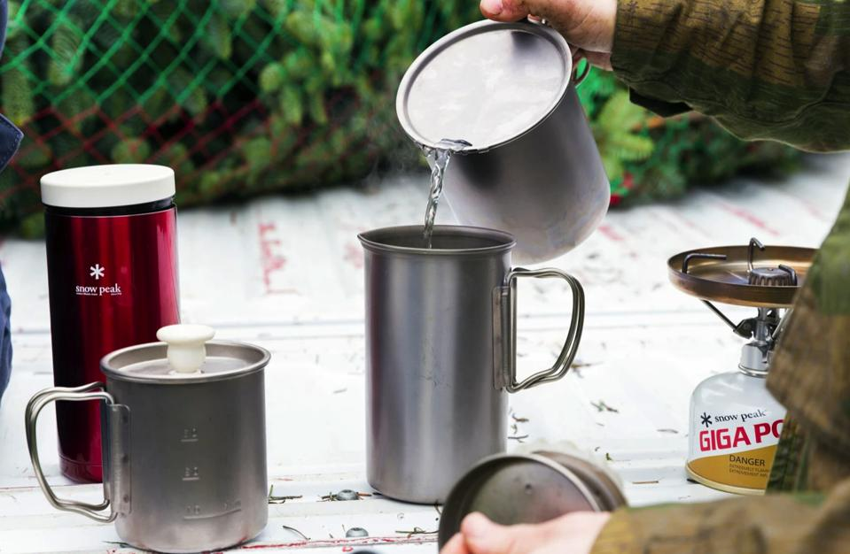 A woman pours hot water into the Snow Peak French press