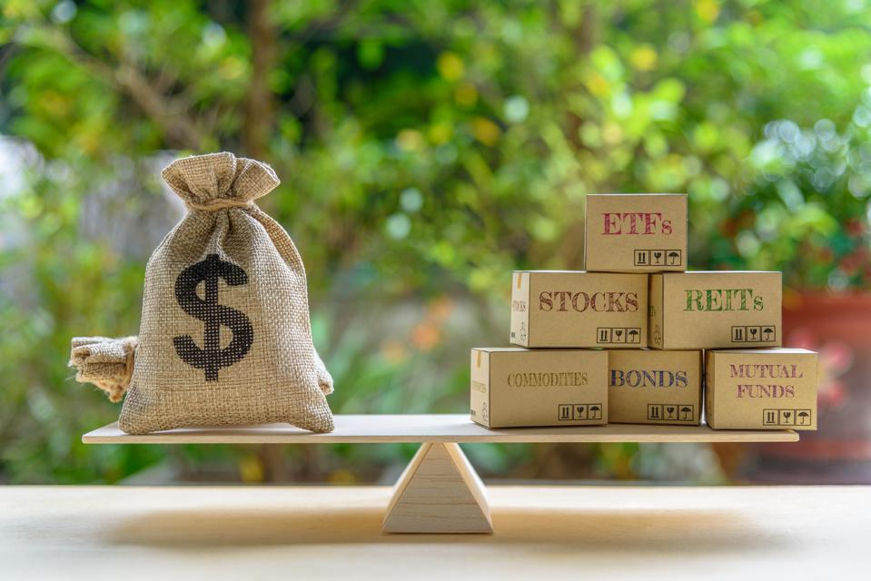 Portfolio management and asset allocation concept : Dollar bag, financial products on balance scale e.g ETFs, REITs, stocks, commodities, bonds, mutual funds, depicts balancing between risk and return