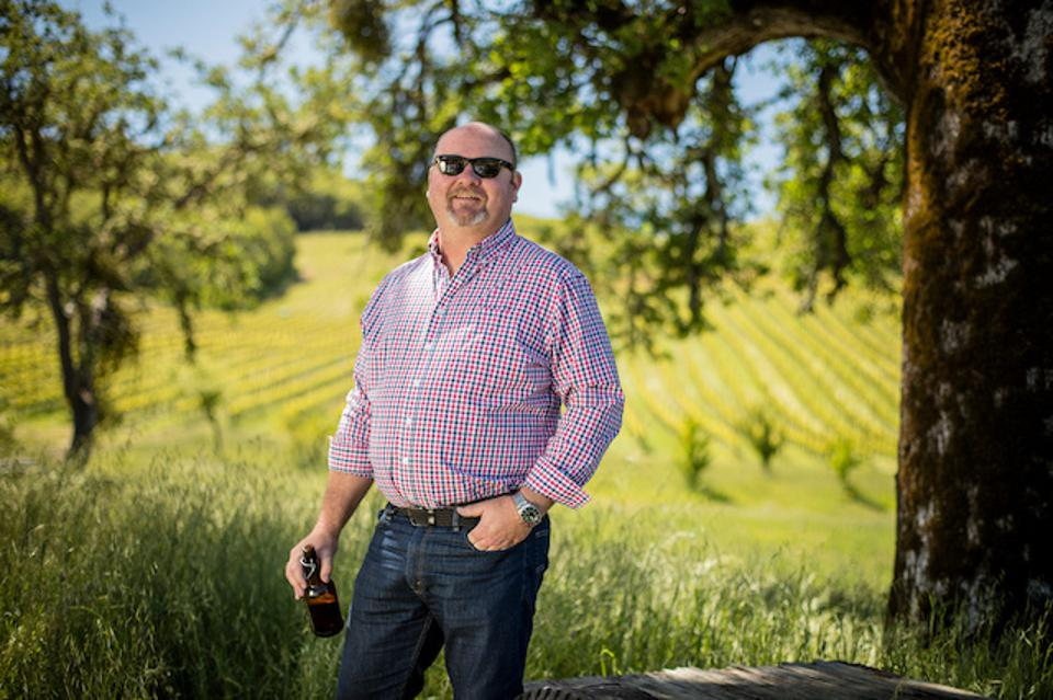 Jeff Cichocki holding a bottle in a vineyard