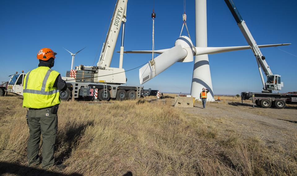 Engineers and technicians lower the rotor and blades off a wind turbine.