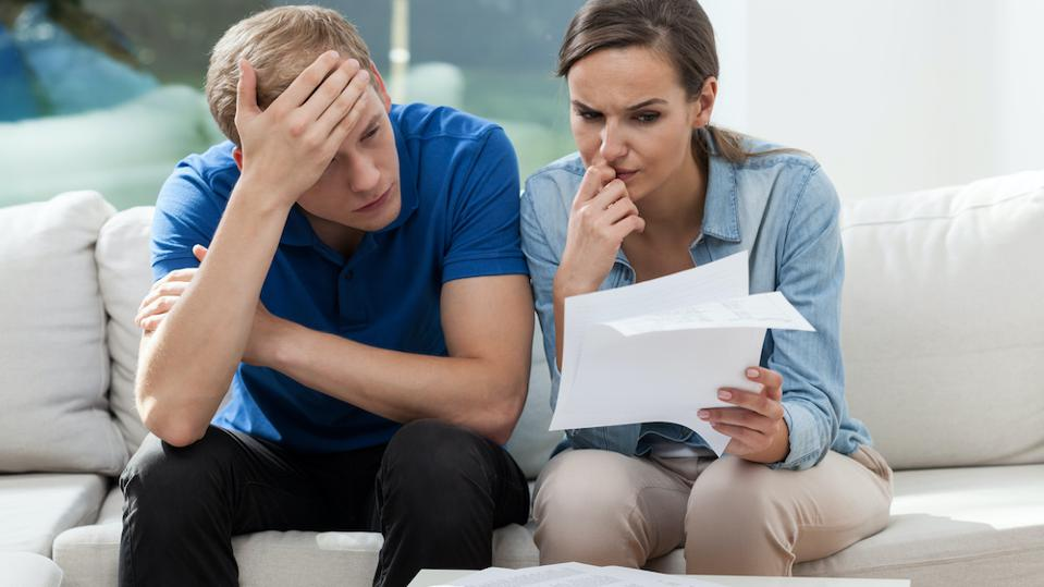 worried young couple paying bills