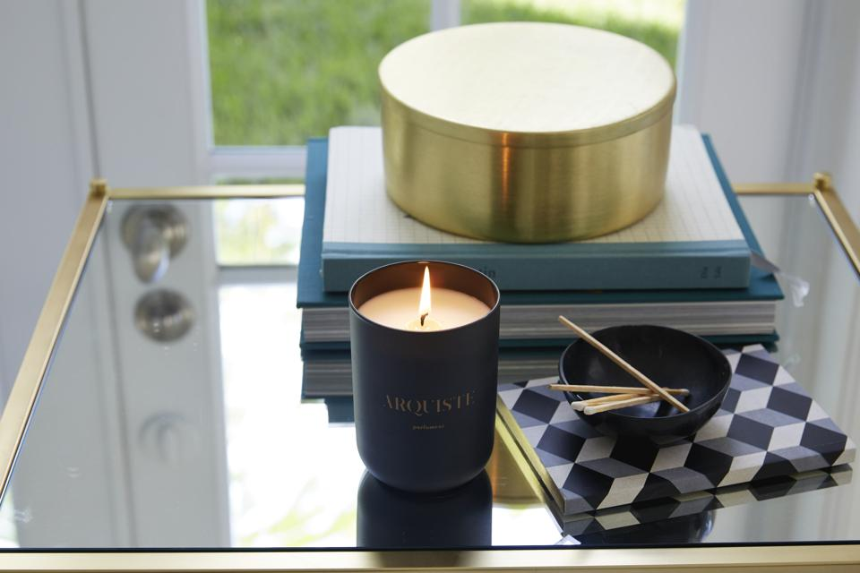 black candle on glass table with gold box and matches