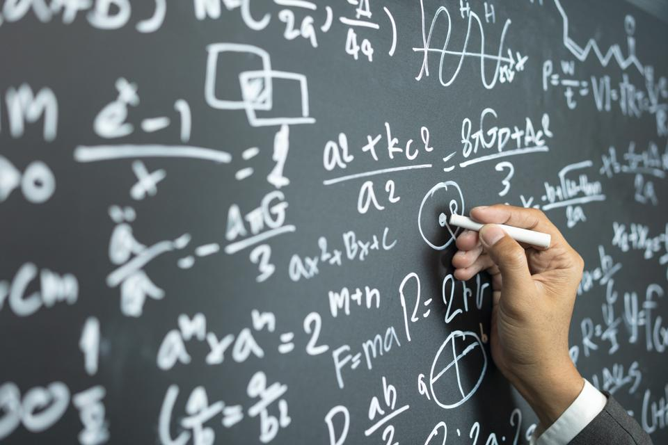 professor writing on the board while having a chalk and blackboard lecture