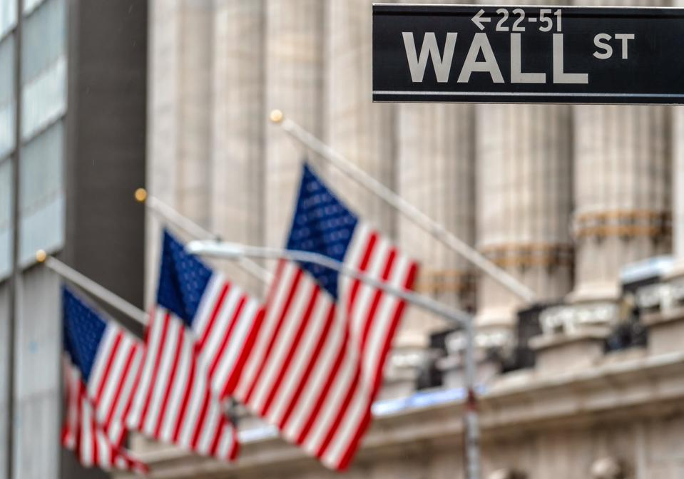 Wall Street ″WALL ST″ sign over American national flags in front of NYSE stock market exchange