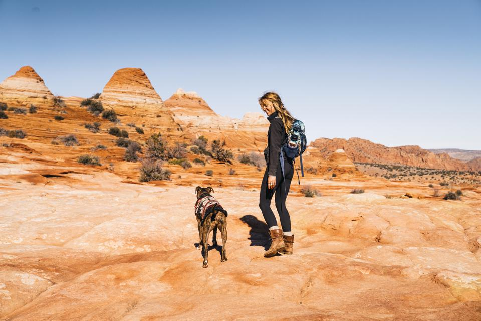 Young woman hiking with dog, Grand Staircase Escalante National Monument