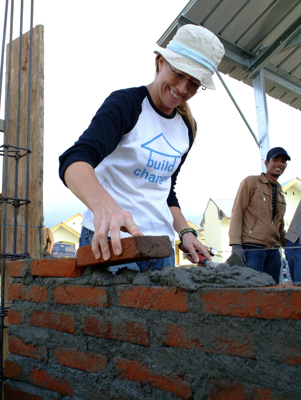woman laying bricks to build a home