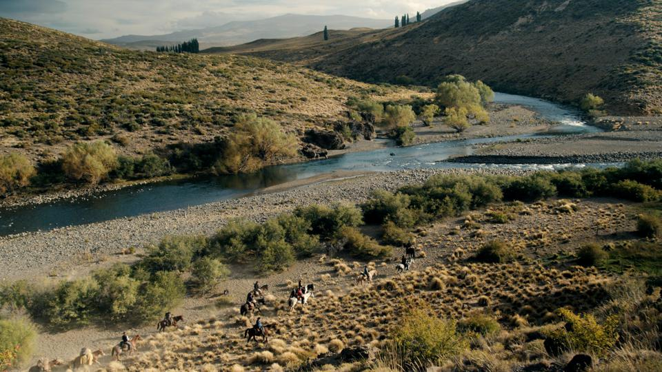 People on horseback ride past a confluence of rivers