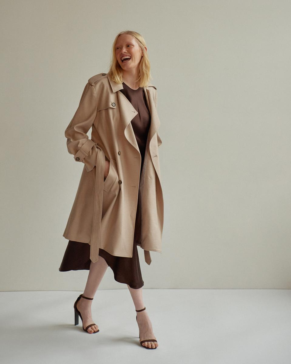 Model wearing a trench over a dress smiling