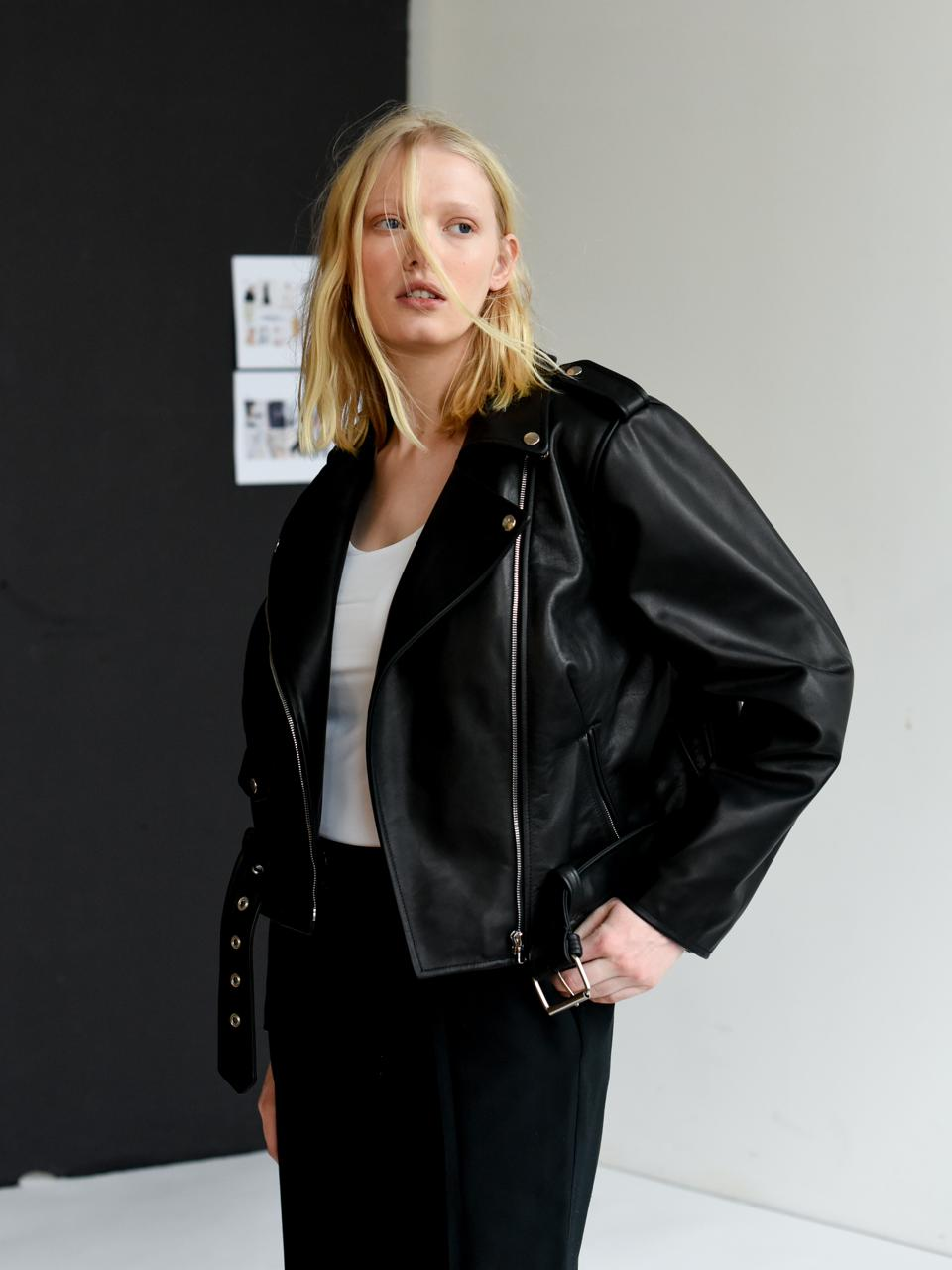 A model wearing a leather coat looking off in the distance