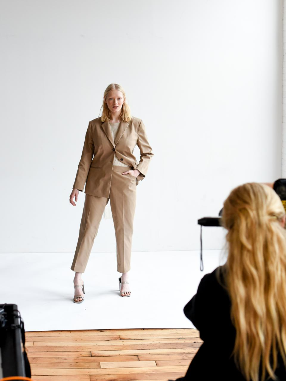 Model being photographed in a beige pant suit