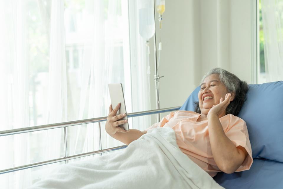 Happy senior woman in bed using tablet to talk with someone